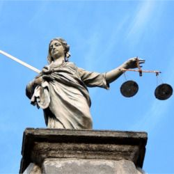 statue of a bindfolded lady justice with sword and scales against a blue sky