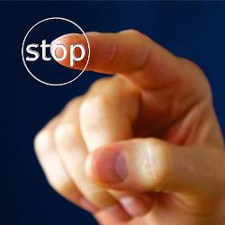 hand pushing a stop button with their finger