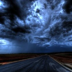 dark thunderstorm clouds rolling over a long highway over a flat horizon