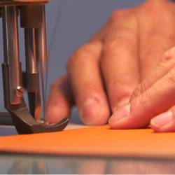 pair of hands using a sewing machine to sew together leather pieces