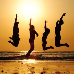 Silhouette of a group of people on a beach jumping into the sunset