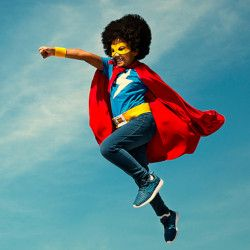 young girl dressed as a superhero with powers flying through the sky