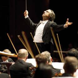 music conductor directing a symphony orchestra