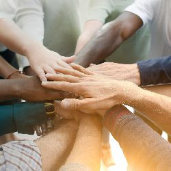 several people joining hands in a circle together in teamwork