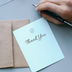 Person writing in a thank you card