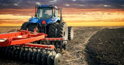 blue and red tractor on a crop field at sunset