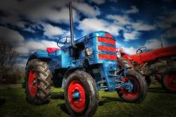 Blue tractor set against ominous clouds on a farm field