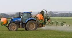 Tractor on an agricultural farm field spraying pesticides