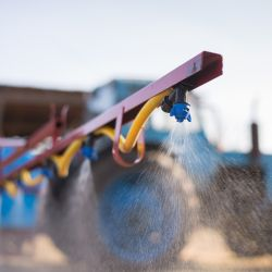 arm of a tractor fitted with a spray nozzle being used to disperse pesticides on a farm field