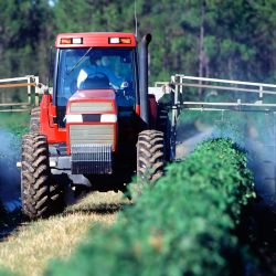 tractor on a farm field applying pesticide spray to crops