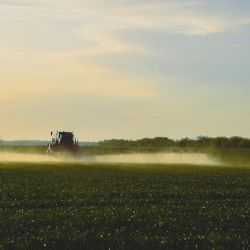 tractor spraying herbicide on farm field crops at sunset