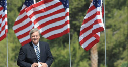 Tom Vilsack in front of some American flags.