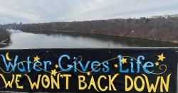 """A sign over the Mississippi that reads, """"water gives life, we, won't back down"""""""