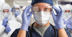Woman with mask and lab goggles.