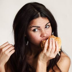 woman eating a fast food hamburger