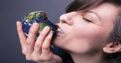 woman eating a pastry in the shape of the earth