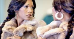 woman in a fur coat glancing at herself in a mirror