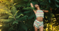 woman modeling clothes in front of greenery