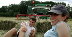 Young farmers sitting in a hay field near a tractor