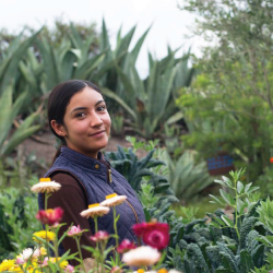 woman standing in a garden field with flowers and agave