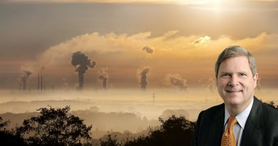 Tom Vilsack against a factory spewing pollution into the air