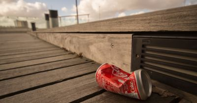 crushed coca cola soda pop can on a wooden boardwalk in the sun
