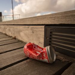 Crushed soda can on a boardwalk