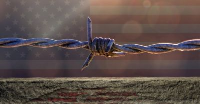 Brick wall topped with barbed wire in front of the American flag
