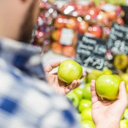man shopping in a grocery store comparing two green apples in the produce department