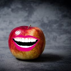 An open mouth with pink lips on a red and yellow apple