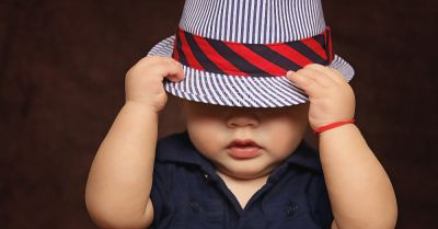 young baby wearing a striped fedora hat over their eyes