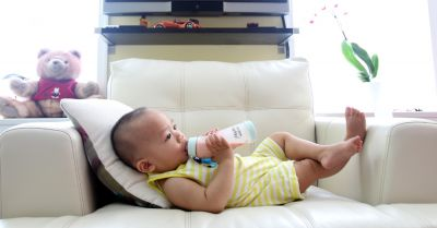 infant child drinking from a bottle