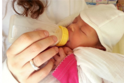 Baby being fed with bottle