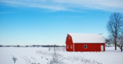 red barn in the middle of a farm field covered in snow in the winter time