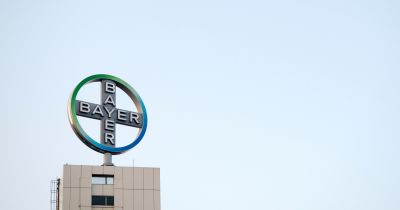 logo for Bayer on a factory building against an overcast gray sky