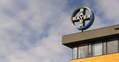 corner of a building against a cloudy sky with the BAYER logo