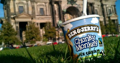 pint of Ben and Jerrys ice cream in a grassy field by a large gray building