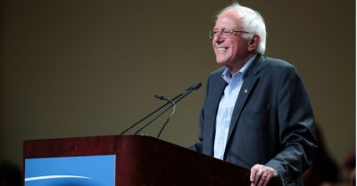 Bernie Sanders at a podium smiling to the crowd