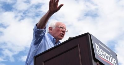 Bernie Sanders at a podium during a campaign speech against a blue and cloudy sky
