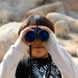 Boy holding a pair of binoculars up to his eyes