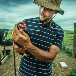 Farmer holding a chicken in Colorado