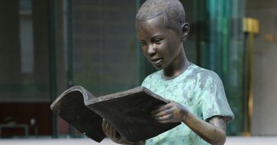 Statue of a child reading a book