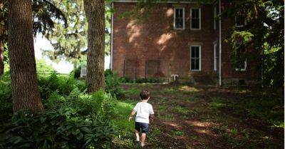 boy walking through the woods beside a brick house