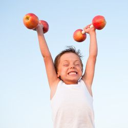 young boy with apple barbell weights