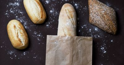 several styles of baked bread on a black table with bits of flour and a paper bag