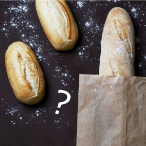 assorted loaves of bread with bits of flour and a paper bag with a question mark