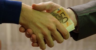 two hands shaking in a bribe with euro bills