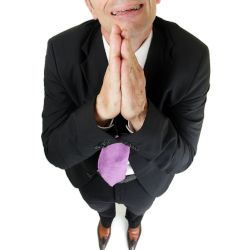 man dressed in business suit pleading and crying
