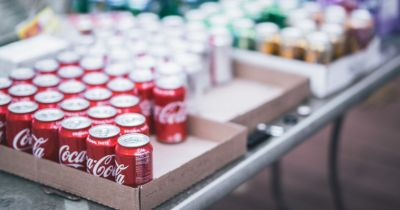 red aluminum cans of coca cola in a cardboard carton on a table