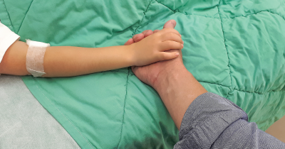 Sick child holding parents hand.